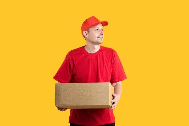Kurier mężczyzna w czerwonym mundurze, trzymając w rękach puste pudełko corton na żółto