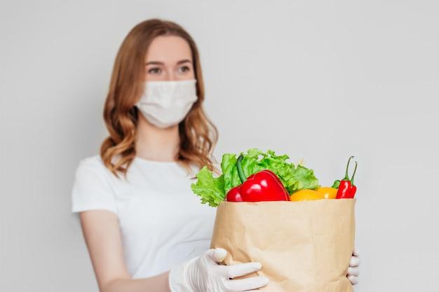 Kurier młoda kobieta ubrana w maskę medyczną trzyma papierową torbę z jedzeniem, warzywami, papryką, chili, sałatą na białym tle nad jasnoszarą przestrzenią, koncepcja dostawy żywności