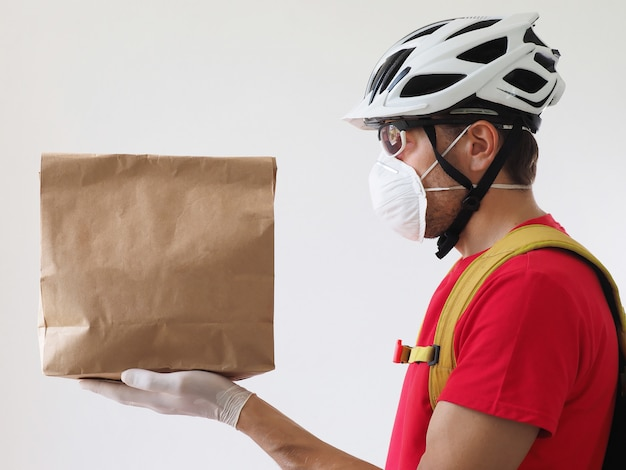 Kurier rowerzysta nosi maskę, a rękawiczki dostarcza papierową torbę. usługa dostarczania podczas koronawirusa kwarantanny.