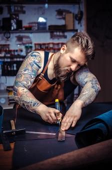 Kurier skórzany pracuje nad nowym produktem skórzanym w garbarni
