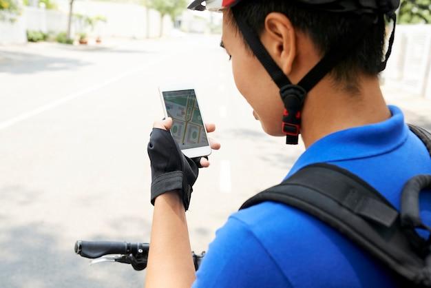 Kurier sprawdzający miejsce docelowe na mapie w smartfonie