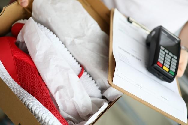 Kurier trzyma buty do biegania i przenośny terminal