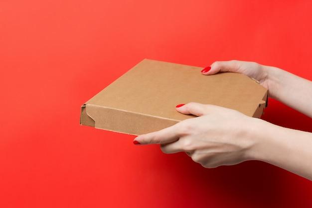 Kurier trzyma pizzy pudełko w rękach odizolowywać na czerwonym tle