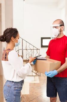 Kurier w czerwonym t-shircie dostarczając pudełko do klienta. kobieta płaci za pomocą aplikacji na telefon.