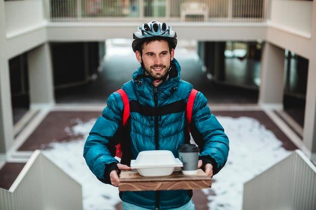 Kurier w domu z pizzą, kanapką i napojami. dostawa do domu rowerem.