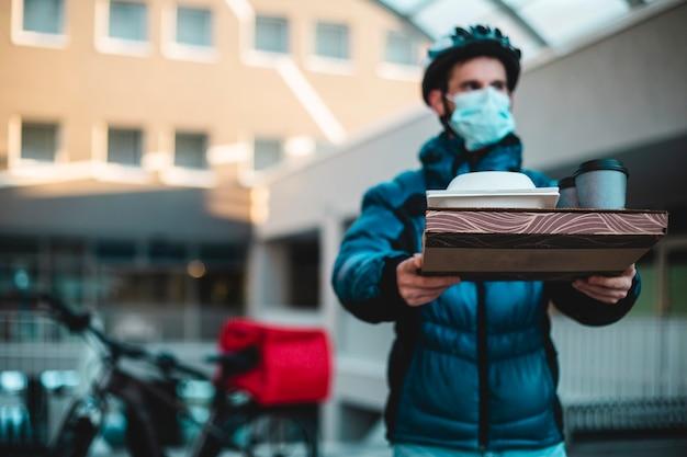 Kurier w domu z pizzą, kanapką, napojami i maską chroniącą przed koronawirusem. covid-19, epidemia, dostawa do domu, dostawa jedzenia