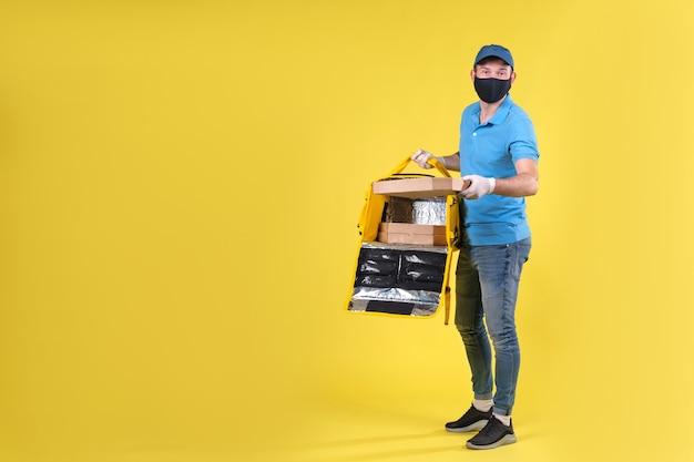 Kurier w masce antywirusowej i rękawiczkach do dostarczania żywności medycznej z żółtą otwartą torbą termosową