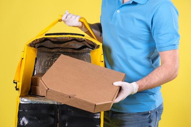 Kurier w masce antywirusowej i rękawiczkach do dostarczania żywności medycznej
