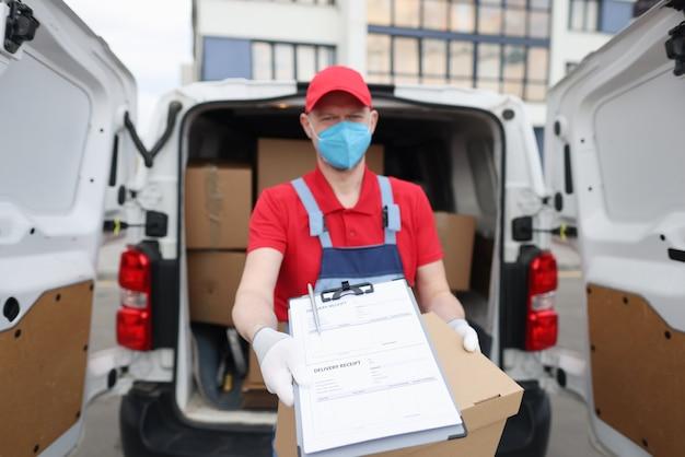 Kurier w masce medycznej i rękawiczkach wyciąga dokumenty z dowodem dostawy