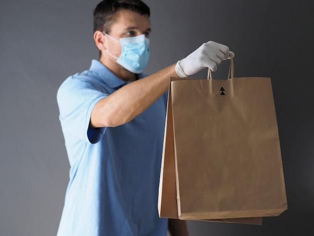 Kurier w masce ochronnej i rękawiczkach medycznych dostarcza jedzenie na wynos podczas pandemii koronawirusa covid-19.