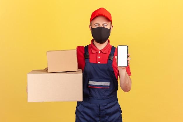 Kurier w mundurze i masce ochronnej na twarzy trzymający i pokazujący kartony i smartfon