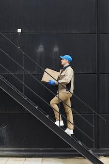 Kurier w mundurze wchodzący po schodach i niosący karton