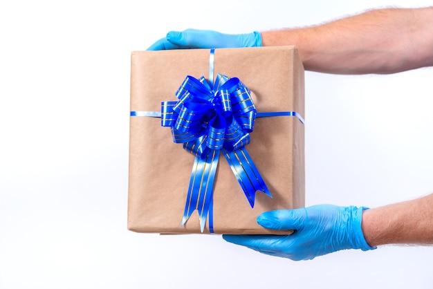 Kurier w niebieskich rękawiczkach posiada pudełko prezentowe