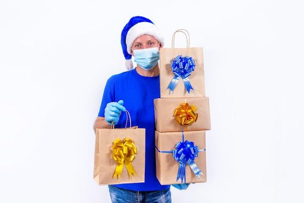 Kurier w niebieskim mundurze, ochronnej masce medycznej, rękawiczkach i czapce mikołaja trzyma pudełka na prezenty