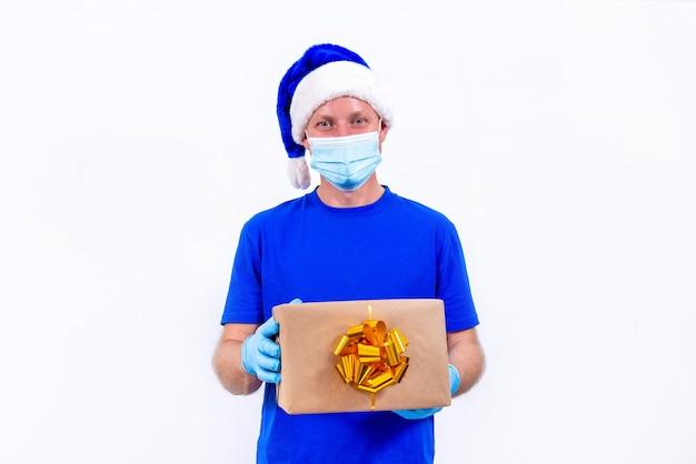 Kurier w niebieskim mundurze, ochronnej masce medycznej, rękawiczkach i czapce świętego mikołaja trzyma pudełko