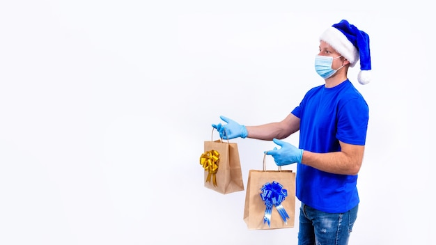 Kurier w niebieskim mundurze, ochronnej masce medycznej, rękawiczkach i czapce świętego mikołaja trzyma woreczki na prezenty