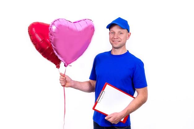 Kurier w niebieskim mundurze trzyma czerwone pudełko w kształcie serca i balon na walentynki
