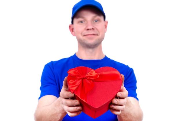 Kurier w niebieskim mundurze trzyma czerwone pudełko w kształcie serca na walentynki. dostawa do domu