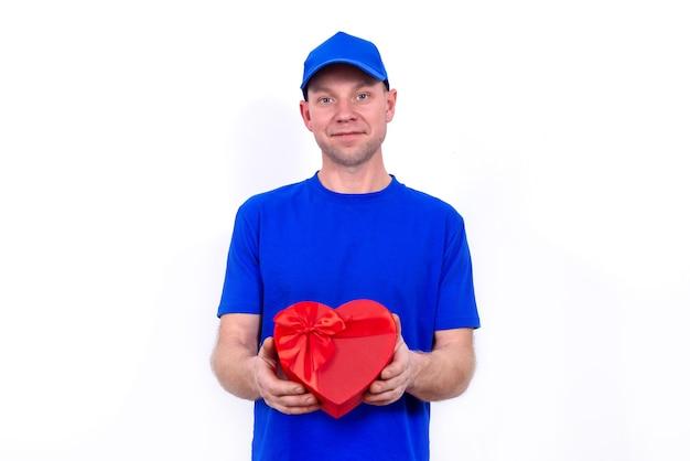 Kurier w niebieskim mundurze trzyma czerwone pudełko w kształcie serca na walentynki