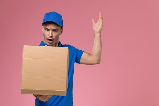 Kurier w niebieskim mundurze, trzymając pudełko z jedzeniem, otwierając je na różowej, jednolitej dostawie usług