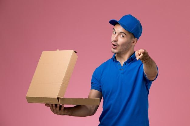 Kurier w niebieskim mundurze, trzymając pudełko z jedzeniem, otwierając je na różowym, mundurze pracownika
