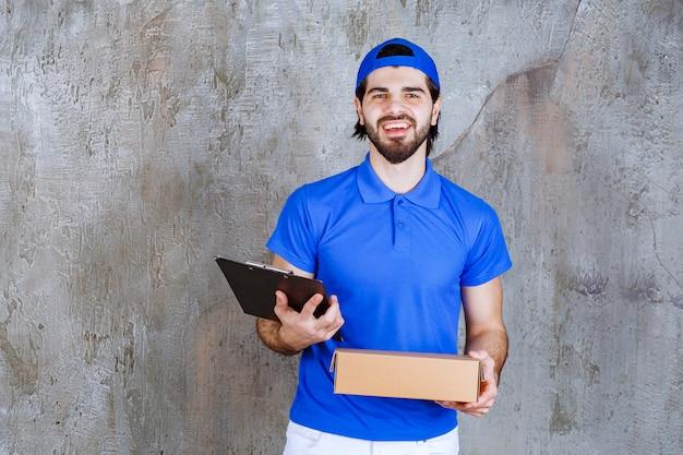 Kurier w niebieskim mundurze trzymający pudełko na wynos i czytający adres