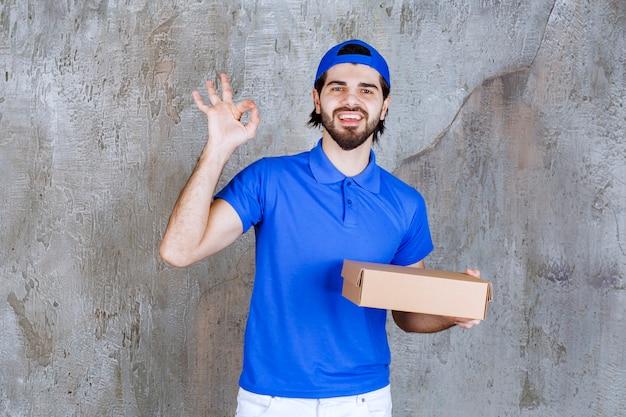 Kurier w niebieskim mundurze trzymający pudełko na wynos i pokazujący znak pozytywnej dłoni.