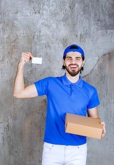 Kurier w niebieskim mundurze trzymający pudełko na wynos i prezentujący swoją wizytówkę