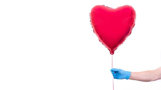 Kurier w ochronnych rękawiczkach trzyma balon w kształcie serduszka na walentynki.