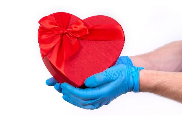 Kurier w ochronnych rękawiczkach trzyma czerwone pudełko w kształcie serca na walentynki.