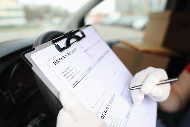 Kurier w rękawiczkach wypełnia pokwitowanie dostawy za pomocą zbliżenia na długopis