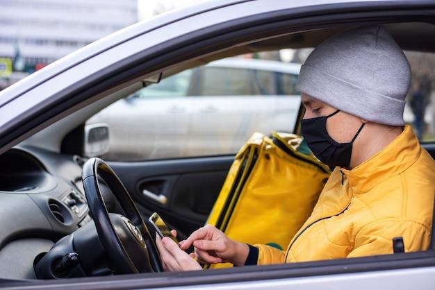 Kurier w samochodzie z czarną maską medyczną ma na telefonie, plecak z dostawą na siedzeniu. usługa dostawy jedzenia