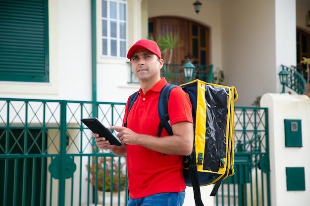 Kurier w średnim wieku szuka domu i trzyma tablet. zamyślony dostawca ubrany w czerwoną czapkę i koszulę i niosący żółtą torbę termiczną z ekspresowym zamówieniem. dostawa i koncepcja zakupów online