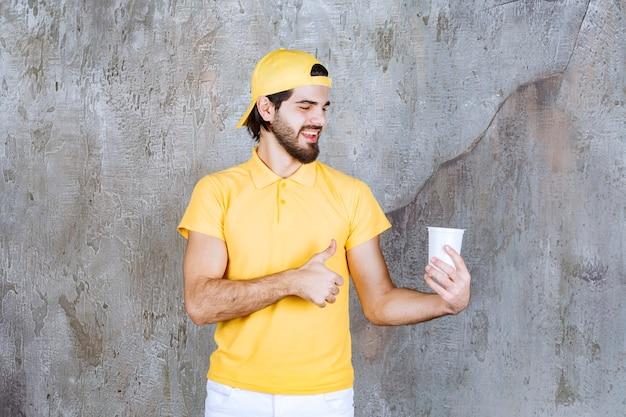 Kurier w żółtym mundurze trzymający jednorazowy kubek i pokazujący pozytywny znak ręki.