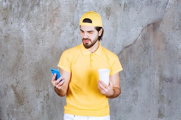 Kurier w żółtym mundurze trzymający jednorazowy kubek i przyjmujący zamówienie przy swoim telefonie.