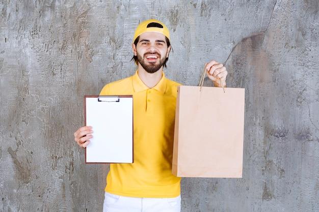 Kurier w żółtym mundurze trzymający kartonową torbę na zakupy i proszący o podpis