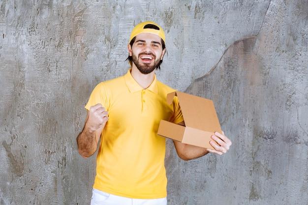 Kurier w żółtym mundurze trzymający otwarte kartonowe pudełko i cieszący się produktem