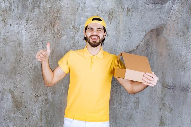 Kurier w żółtym mundurze trzymający otwarte kartonowe pudełko i cieszący się produktem.