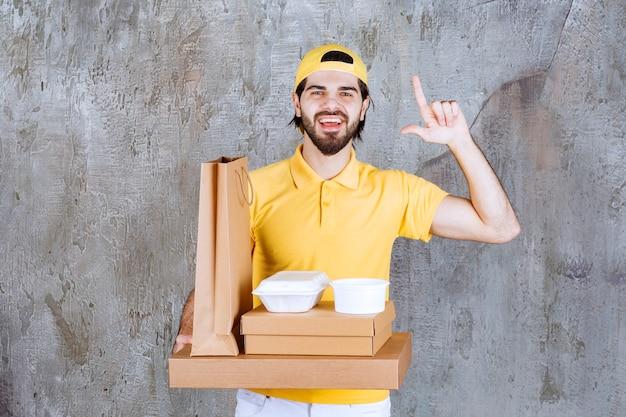Kurier w żółtym mundurze trzymający paczki na wynos i torbę na zakupy i wygląda na zdezorientowanego lub myślącego