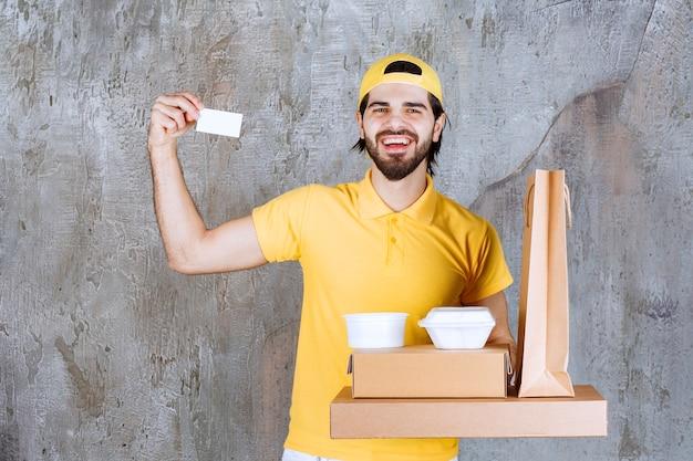Kurier w żółtym mundurze trzymający paczki na wynos i torbę na zakupy oraz prezentujący swoją wizytówkę