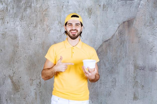 Kurier w żółtym mundurze trzymający plastikowy kubek