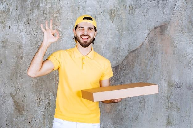 Kurier w żółtym mundurze trzymający pudełko po pizzy na wynos i pokazujący pozytywny znak ręki