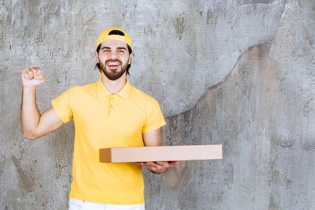Kurier w żółtym mundurze trzymający pudełko po pizzy na wynos i pokazujący pozytywny znak ręki.