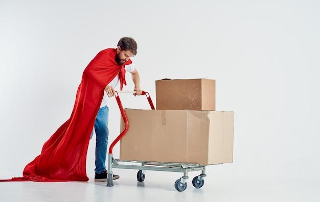 Kurier z kartonami w wózku i czerwonym płaszczu superbohatera