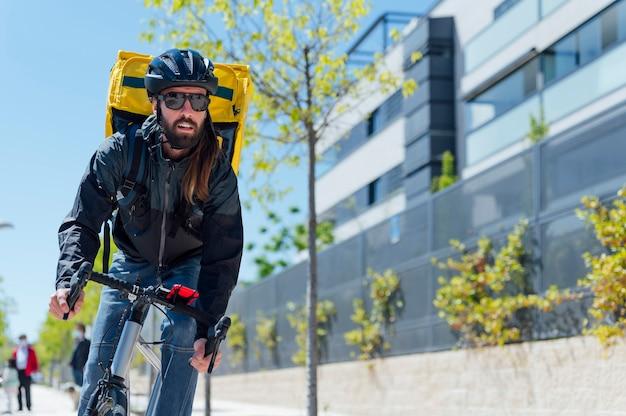 Kurier z rowerem dostarczający paczki po mieście. skopiuj miejsce.