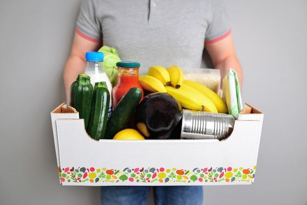 Kurier ze świeżymi produktami na jasnym tle zbliżenie usługa dostawy żywności darowizna pudełko z dostawami jedzenie dla ludzi koncepcja dostawy spożywczy kurier człowiek z pudełkiem spożywczym