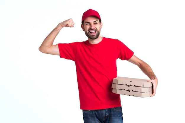Kuriera mężczyzna trzyma stos pudełek po pizzy i pokazuje mięśnie