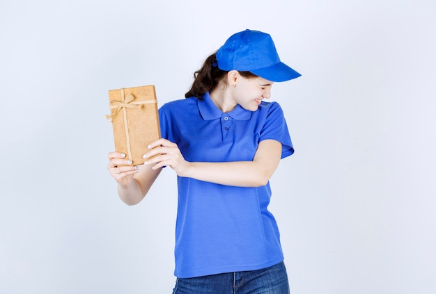 Kurierka odsuwa od niej brązowe pudełko prezentowe, jednocześnie zamykając oczy przed białą ścianą