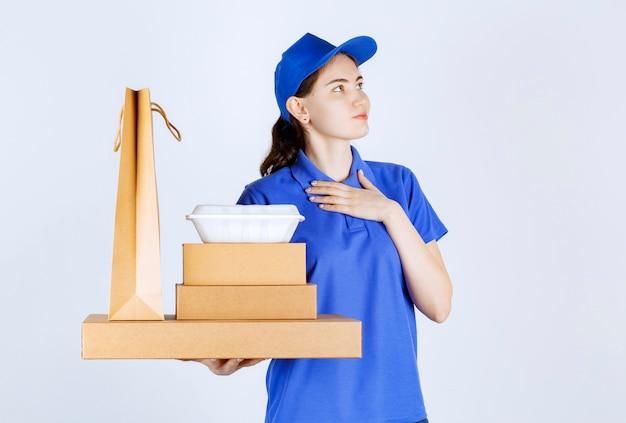 Kurierka patrzy w lewą stronę i kładzie lewą rękę blisko piersi, trzymając pudełka i torbę w prawej ręce