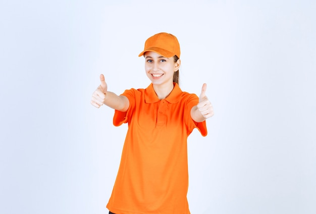 Kurierka ubrana w pomarańczowy mundur i czapkę pokazującą kciuk w górę